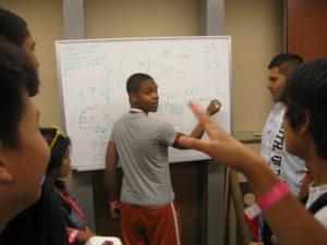 A ProCSI 2010 solves a problem on a whiteboard