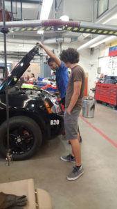Two ProCSI 2015 members look under the hood of a car